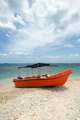 Orange panga / fishing boat on coral beach in Sri Lanka Asia