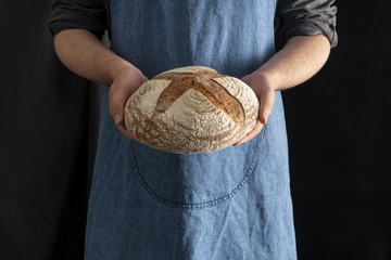 Baker Holding a Whole Sourdough Rye Bread on Black Background