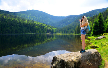 Nature photographer taking picture photos with DSLR camera moraine lake Kleiner Arbersee in National park Bavarian forest. Germany.
