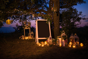 Night decorated zone outdoor; candles, lantern, board, vase, jar, lead board