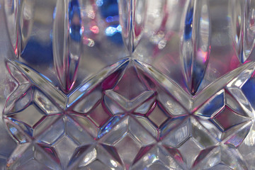 Macro abstract background of beautiful lead crystal glass with geometric cut surface patterns reflecting colorful bokeh