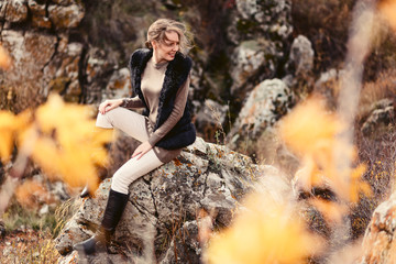 beautiful young woman sitting on the rocks in autumn