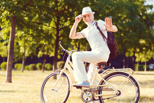 Hey mate. Cheerful elderly gentleman smiling while sitting on his bicycle and waving his hand while welcoming somebody outdoors.