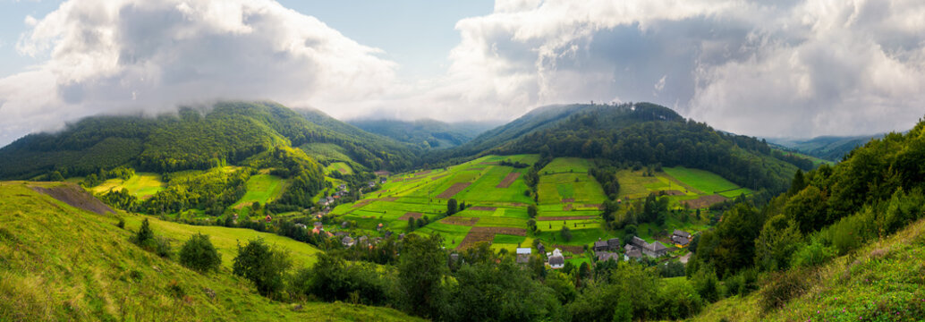 panorama of a rural area in mountains. gorgeous forenoon with beautiful clouds on the sky. agricultural fields on hills calm and peaceful life concept.