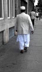 Muslimischer Mann in weißer, traditioneller Kleidung zu Fuß unterwegs