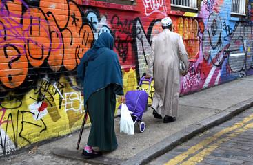 Älteres muslimisches Paar auf einem Gehweg vor einer Mauer mit bunter Street-Art