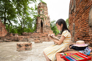 Asian cute girl is study and drawing at archaeological site,field trip,A trip outside of the school(Wat Mahathat,Ayutthaya,Thailand)
