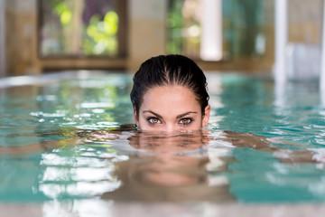Beauty female model peeking out of pool