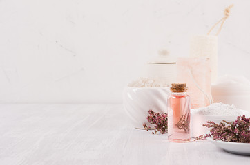 Organic homemade white cosmetics with pink flowers and massage oil on white wooden background, border.