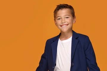Little elegant boy smiling on orange background.