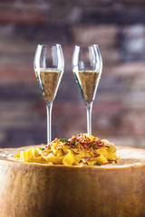 Italian pasta pappardelle with aperitif on a large block of cheese parmesan.