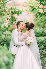 Happy kissing newlyweds under the rose arch.
