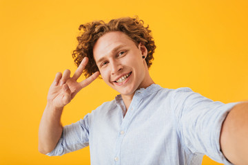 Portrait of happy smiling guy 20s taking selfie photo and showing peace sign, isolated over yellow background