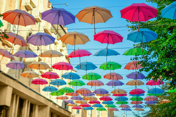 Street installation of multi-colored open umbrellas. The sky of colorful umbrellas. Background colorful urban umbrella street decoration.