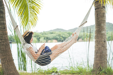 A woman traveler stay on hammock under coconut tree and playing mobile phone