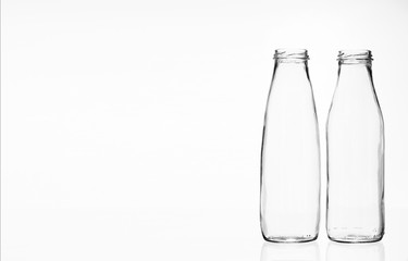 Two empty milk or kefir bottles of different shapes with copy space