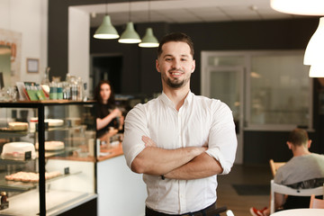 Young male smiling businessman standing with at cafe. Concept of business and success.