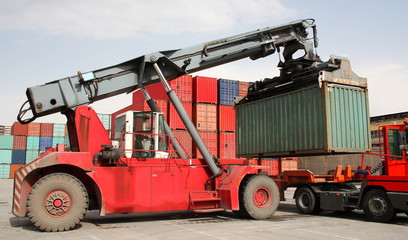 Reach stacker vehicle moving a container into a container terminal area