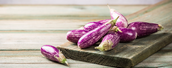 Heap of small eggplant or aubergine vegetable on old wooden background. Healthy food concept with copy space. Banner.