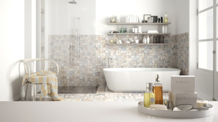 Spa, hotel bathroom concept. White table top or shelf with bathing accessories, toiletries, over blurred vintage classic bathroom, modern architecture interior design