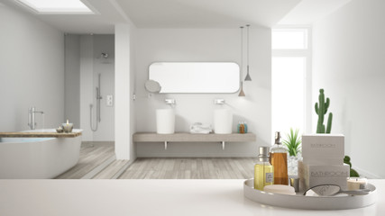 Spa, hotel bathroom concept. White table top or shelf with bathing accessories, toiletries, over blurred minimalist bathroom, modern architecture interior design