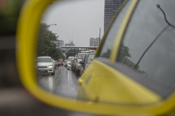 Blurred image of yellow car mirror on the street.