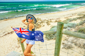 Happy woman waving Australian Flag in a windy day. Mettams Pool in Trigg Beach, North Beach neighborhood near Perth, Western Australia. Tourism in Oceania. Lifestyle female in summer holidays.