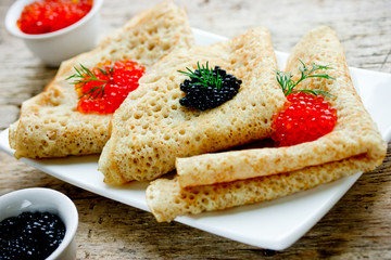 Delicious thin pancakes with red and black caviar close up