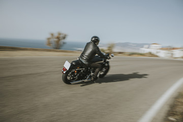 Man in black clothes riding an American motorcycle in a road in the mountain, with blue sky in the background.