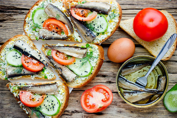 Smoked sprat fried sandwiches with boiled egg, tomato, cucumber and sesame