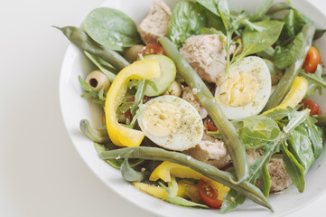 Nicoise salad with tuna, eggs, green beans, yellow bell pepper, red cherry tomato, arugula, cucumber, spinach leaves and olives. Healthy diet concept