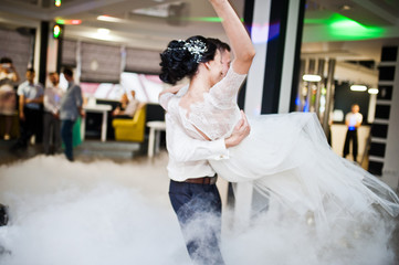 Romantic newly married couple performing their first dance in the restaurant with heavy smoke.