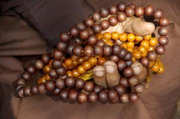 Hand of an old man with Buddhist wooden chain Shwedagon Pagoda Yangon Burma