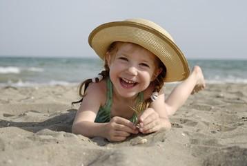 Little girl lies at a sandy beach at the sea