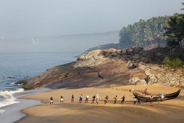 Fishermen pulling in a net, beach south of Kovalam, Vizhinjam in the distance, Malabar Coast, Malabar, Kerala, southern India, India, Asia
