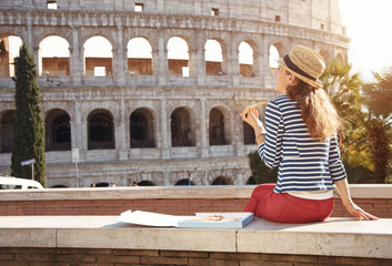young woman in front of Colosseum in Rome, Italy eating pizza