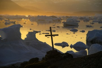Christian cross in front of icebergs in the orange evening light, Parnakajiit, Sermilik Fjord, East Greenland, Arctic