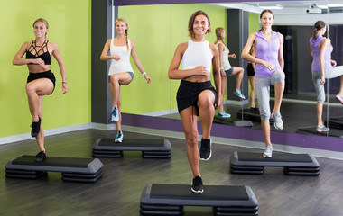 Young fit females working out  with step platforms in gym