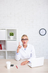 funny female doctor or scientist showing idea sign in office - copy space over white wall