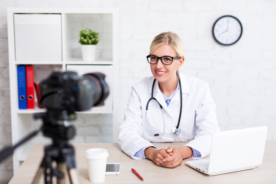 cheerful beautiful woman doctor recording vlog video about medicine