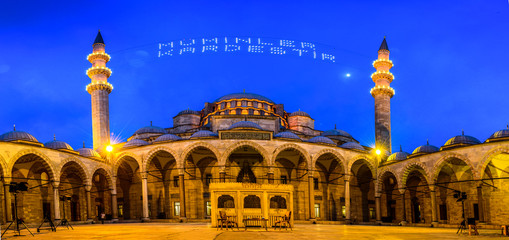 """ISTANBUL, TURKEY - JUNE 4, 2017:Mahya of """"Muslims are brother"""" is written and hung between minarets of Suleymaniye Mosque. Mahya is to write with light especially during ramadan month for muslims"""