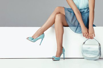 legs woman wearing high heels shoes sitting on bench.