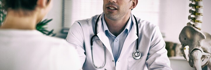 Doctor writing something down while patient is talking