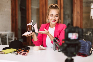 Smiling girl in pink jacket happily showing shoes on heel while recording new fashion video for vlog on camera