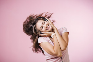 Brown-haired girl with headphones listening to music with closed eyes on pink background