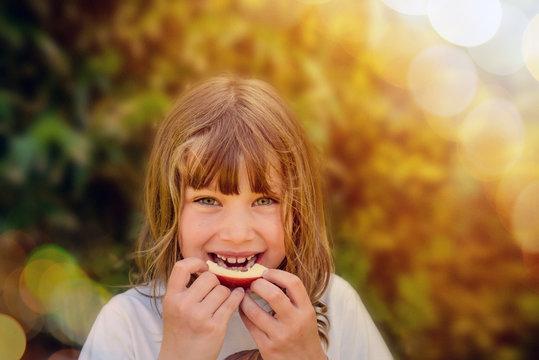 belle enfant croquant une pomme