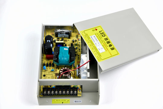 SMPS power supply, power adapter. The new unit is a power source for converters and industrial equipment on a gray background. Chromium element of electricity conversion in industries.