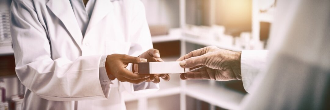 Cropped image of patient hand taking box from pharmacist