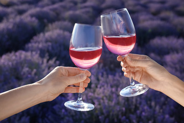 People with glasses of wine in lavender field