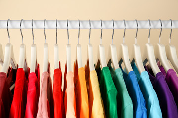 Many t-shirts hanging in order of rainbow colors, closeup